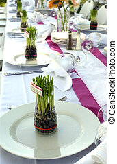 Party Banquet Table With Grass in glass containers used as Centerpieces on Plates