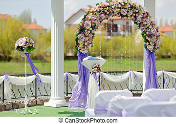 banquet - wedding arbor with a flower arch and white chairs