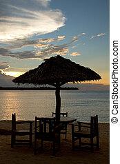 Bar at island beach during sunset