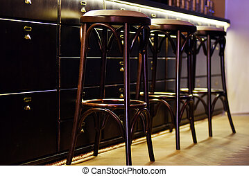 Bar counter with high chairs in cozy restaurant