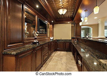 Bar in basement of luxury home with wood cabinetry