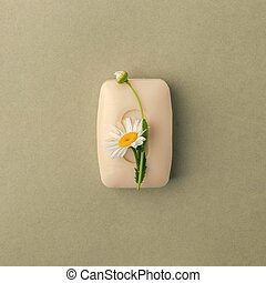 Bar of handmade soap with camomile flowers over green pastel grunge background.