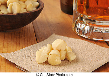Macadamia nuts on a napkin on a bar counter with a mug of beer