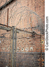 barb wire on an old fence with red brick wall