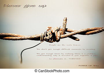 The sharp edges of barb wire with some inspirational words.