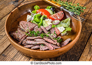 Barbecue beef meat chop rump steak on a wooden plate with vegetable salad. wooden background. Top view