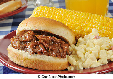 Barbecue beef sandwich with corn on the cob