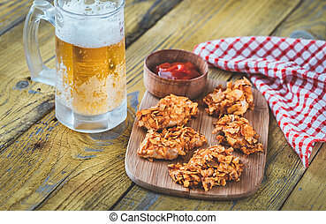 Barbecue chicken bites with mug of beer