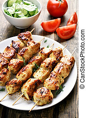 Barbecue, chicken kebab and vegetables on wooden table