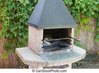 Barbecue fireplace outdoors against of reed fence with maiden grapes
