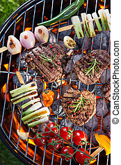 Barbecue grill with beef steaks, close-up.