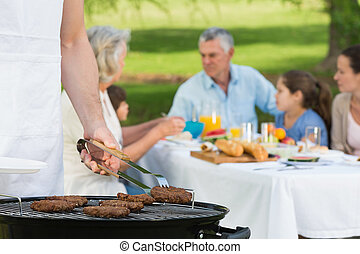 Barbecue grill with extended family having lunch in park - ...