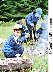 Barbecue in nature, group of children  preparing sausages on fire