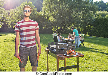 Man, posing next to a barbecue, hoding a fork and pliers, with a group of friends sitting around a picknick table in the background on a sunny summer afternoon.