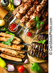 Barbecue menu. Grilled meat skewers, grilled sausages and grilled eggplant with bacon on rustic wooden table. Top view flat lay.