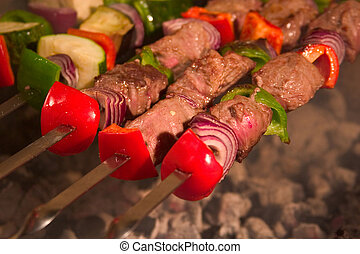 barbecue on skewers - roasted meat, tomatoes and some other ...