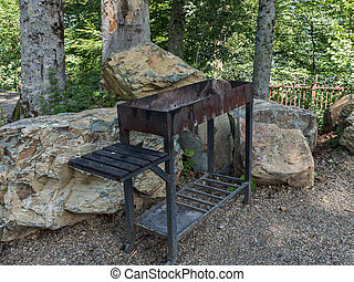Barbecue on the background of large stones in forest