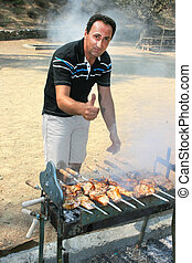 Barbecue - Man roasted barbecue at the charcoal.