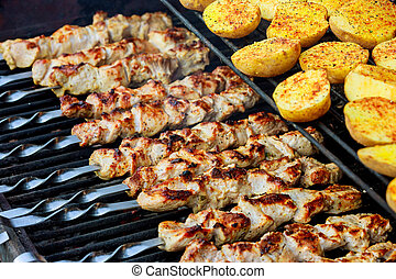 Barbecue skewers with potatoes and meat as well as kebabs are roasted on the grill