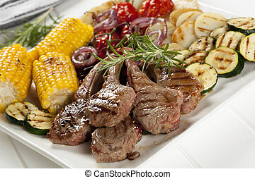 Serving platter of barbecued lamb cutlets and grilled vegetables.