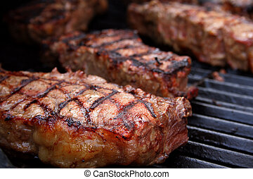 Barbecued Steaks - Thick, juicy steaks on a barbecue grill.