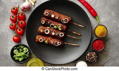 Barbecued turkey kebab decorated with fresh onion and chive...