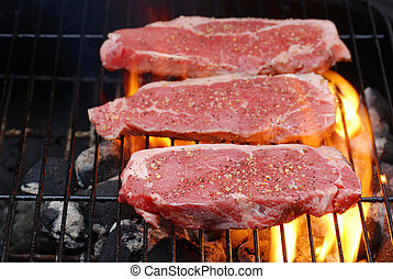 Barbecuing strip loin steaks with flames