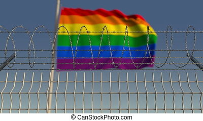 Barbed wire against blurred waving gay pride flag. LGBT...