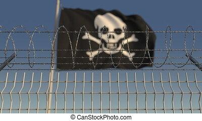 Barbed wire against defocused waving Jolly Roger black...