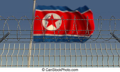 Barbed wire against waving flag of North Korea. 3D rendering...