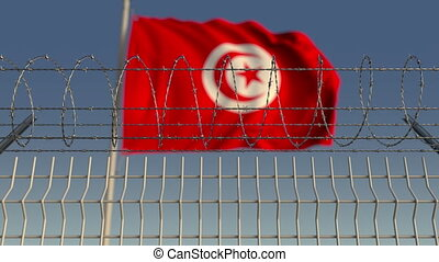 Barbed wire against waving flag of Tunisia. Loopable 3D...