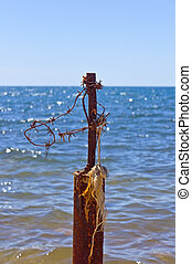 Barbed wire and blue sea - post with the barbed wire on a...