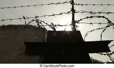 Barbed wire and concrete fence. Pan shot