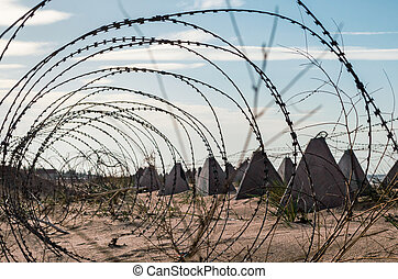 barbed wire and concrete military fence on the beach near the sea in Crimea