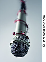 barbed wire around a microphone - closeup of a microphone...