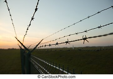 Barbed Wire - Barbed wire fence against clear blue sky