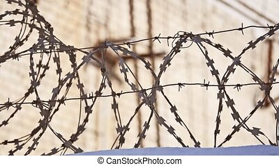 Barbed wire fence at the prison, the sun glare on a...