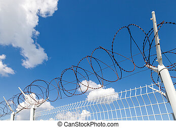 Barbed wire on blue sky background