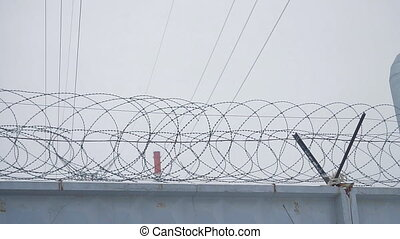 Barbed wire on concrete fence on the background of the grey...