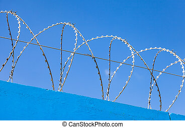 Barbed wire on the fence against a blue sky background