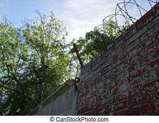 barbed wire over brick fence in spring