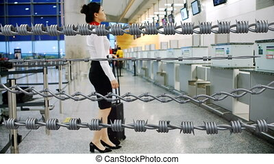 Digital composite video of four barbed wires female air hostess with suitcase walking in airport. Covid 19 coronavirus pandemic travel restrictions concept