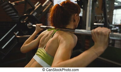 Barbell. Girl squats with a barbell