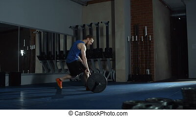 Barbell Lunges - Athletic man lunging with barbell in gym