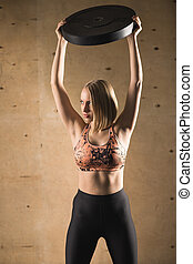 barbell plate raise blonde girl workout at gym exercise