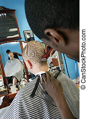 A barber cutting a pattern into a blond man's short hair. Three model releases attached. Third model release is for the photo in the frame on the wall, which has been edited in from an image from my portfolio. Property is a barbershop and tattoo studio - signed property release attached.