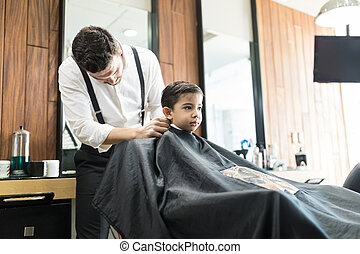 Barber Adjusting Drape On Little Boy In Shop