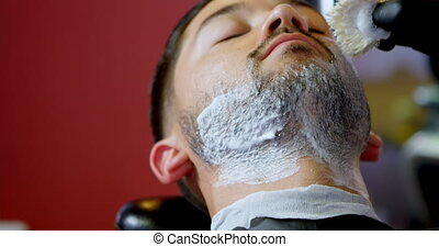 Barber applying shaving cream on client beard 4k - Barber...