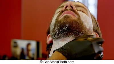 Barber applying shaving cream on mans beard 4k - Barber...