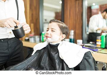 Barber Applying Shaving Foam On Boy's Face In Shop